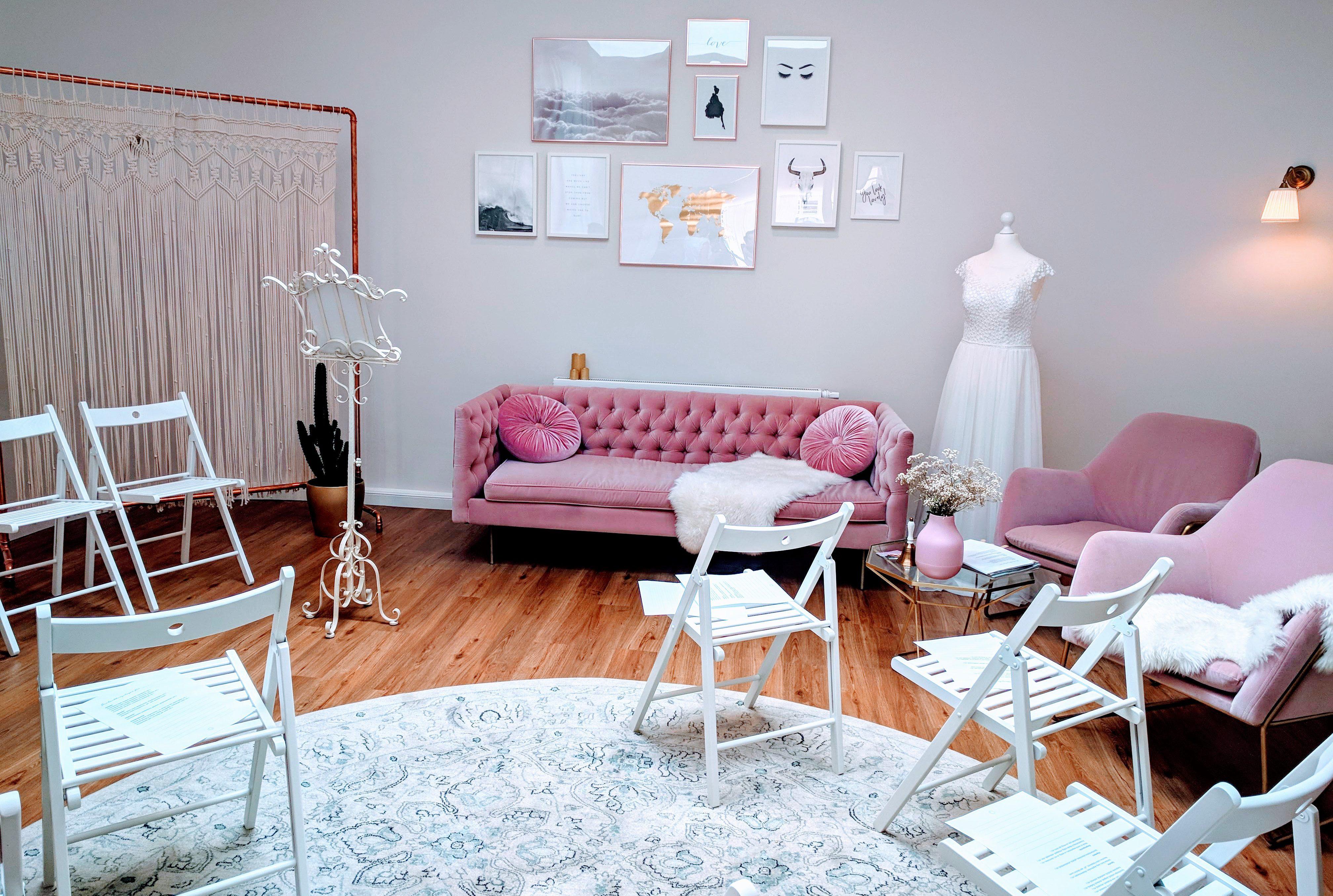 """Das Bild zeigt den Showroom des """"Das Brautstübchen"""" in Remscheid. In der Mitte des Raums stehen weiße Klappstühle, ausgerichtet zu einem Vintage-Trauständer im vorderen Bereich."""